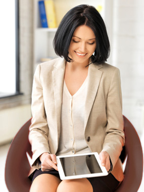 Woman in brown chair using tablet